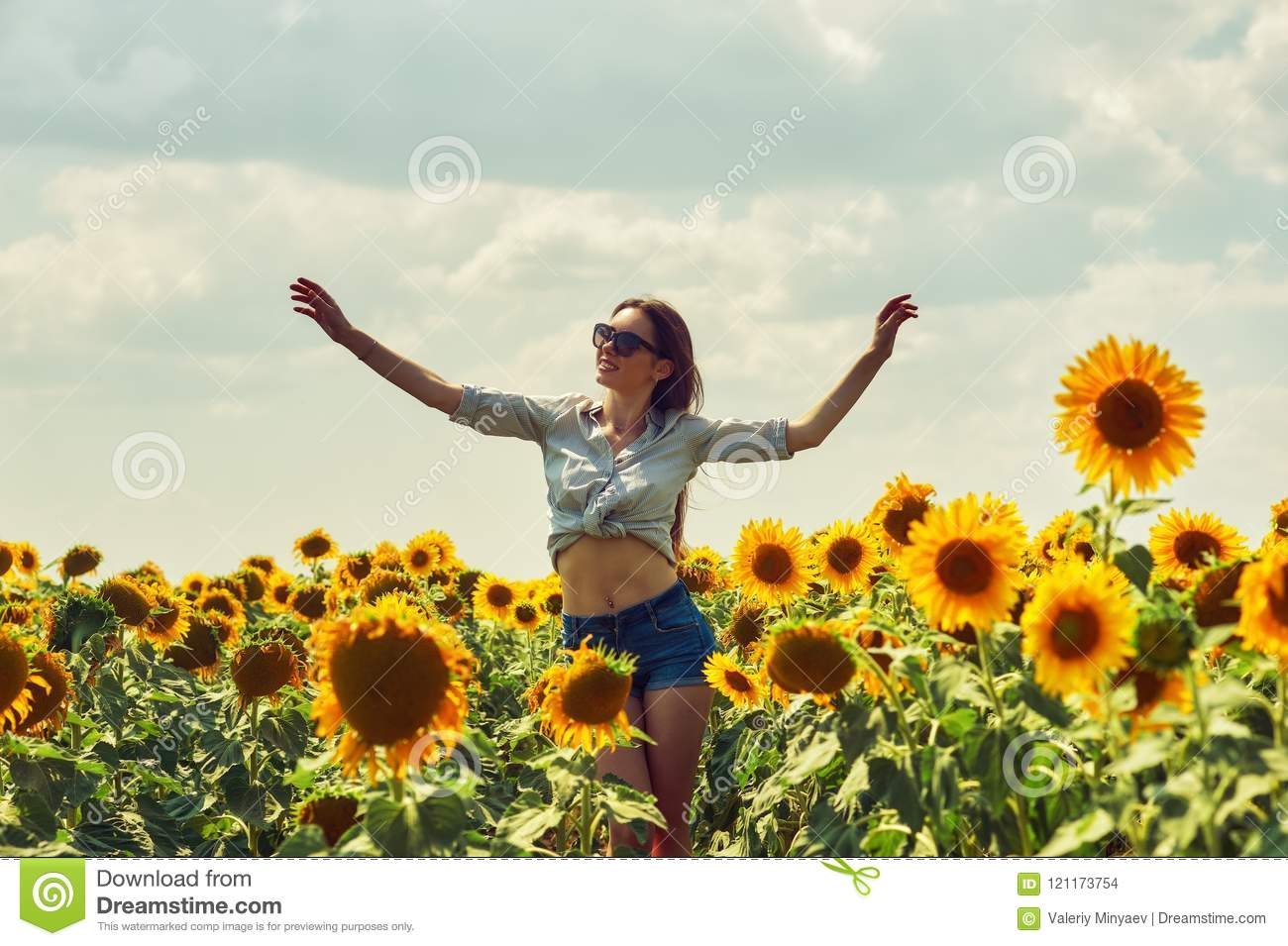 Young attractive girl in the field with sunflowers