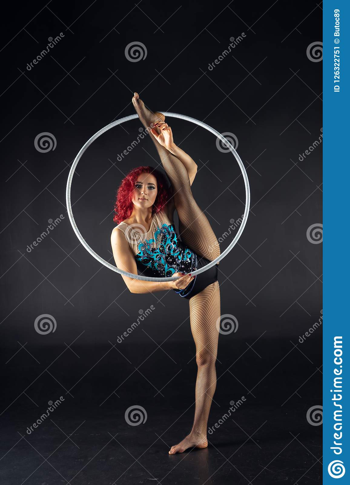 Young attractive girl keep split holding a hoop.