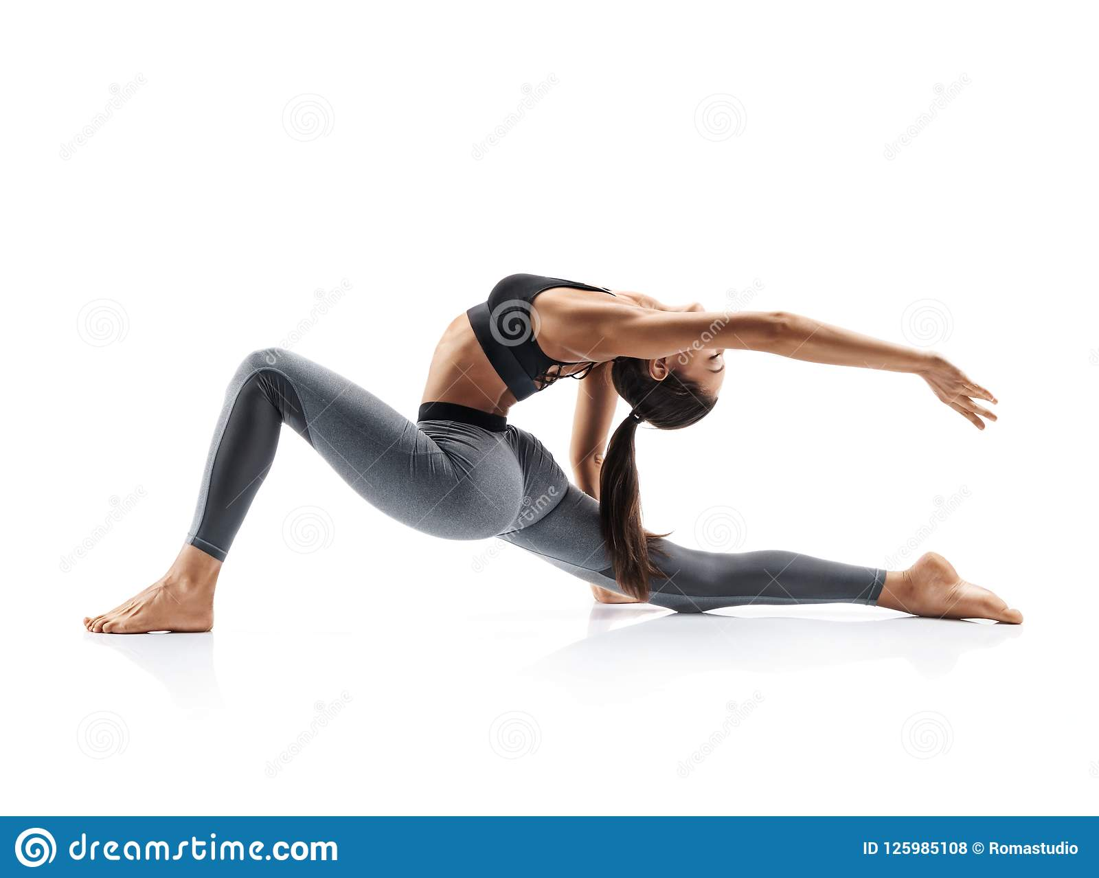 Young attractive girl practicing yoga isolated on white background.