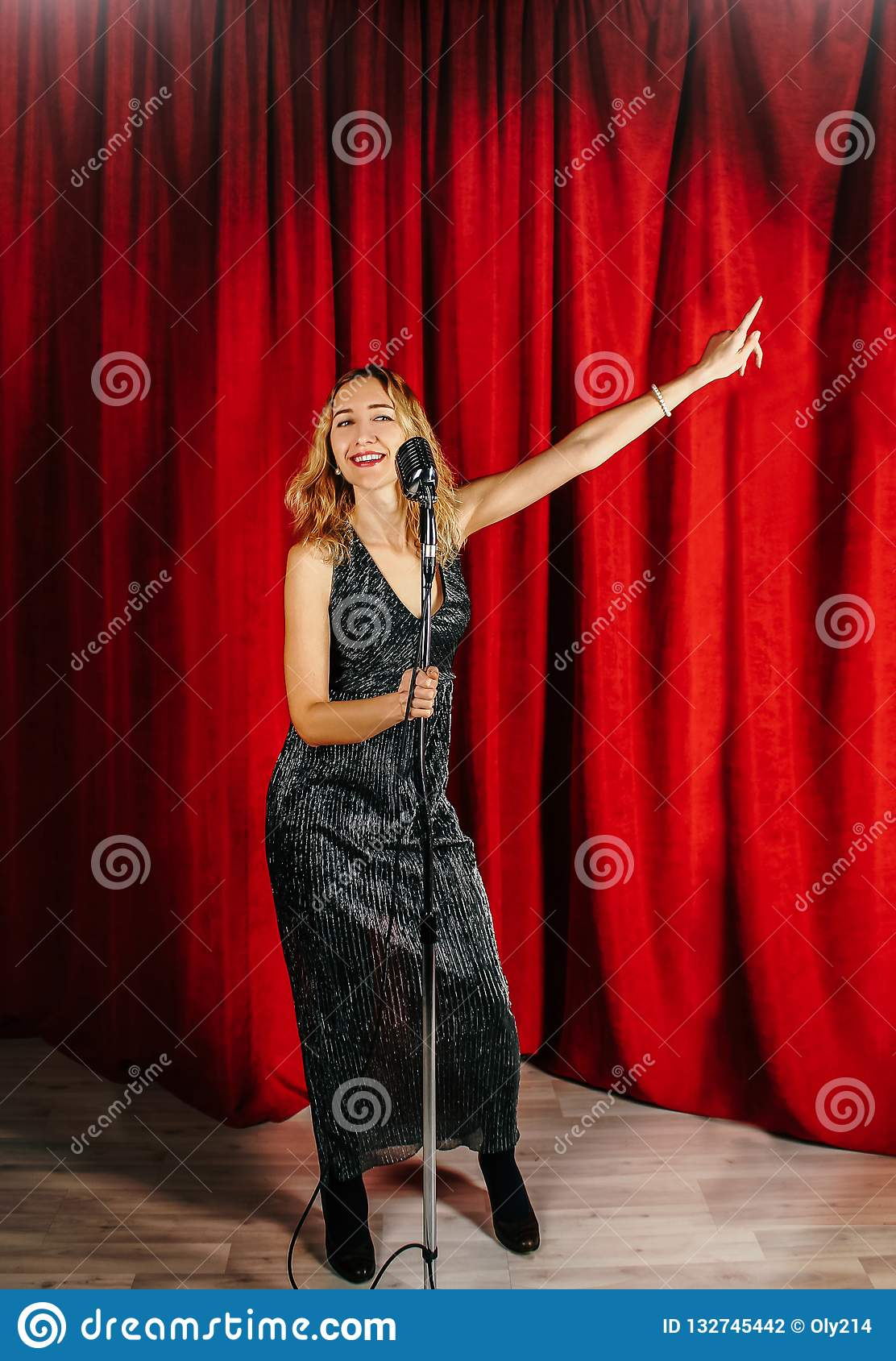 Young attractive girl singing on stage with microphone against t