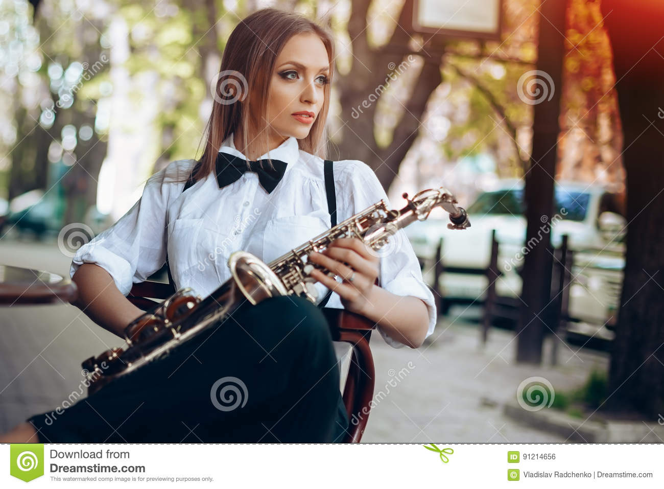 Young attractive girl in white shirt with a saxophone sitting near caffe shop - outdoor in sity. young woman with sax thinkin