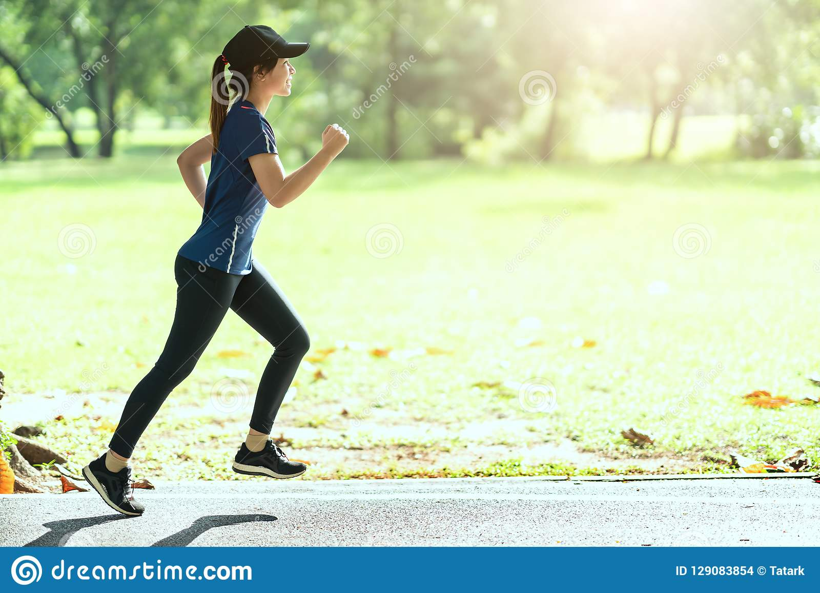 Young attractive happy asian runner woman running in public nature city park wearing sporty sportswear with copy space and sun lig