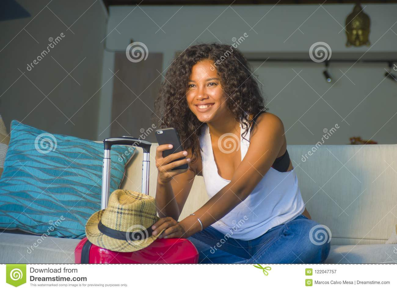 Young attractive and happy black afro American woman at home with suitcase using mobile phone leaving for holidays trip in tourism
