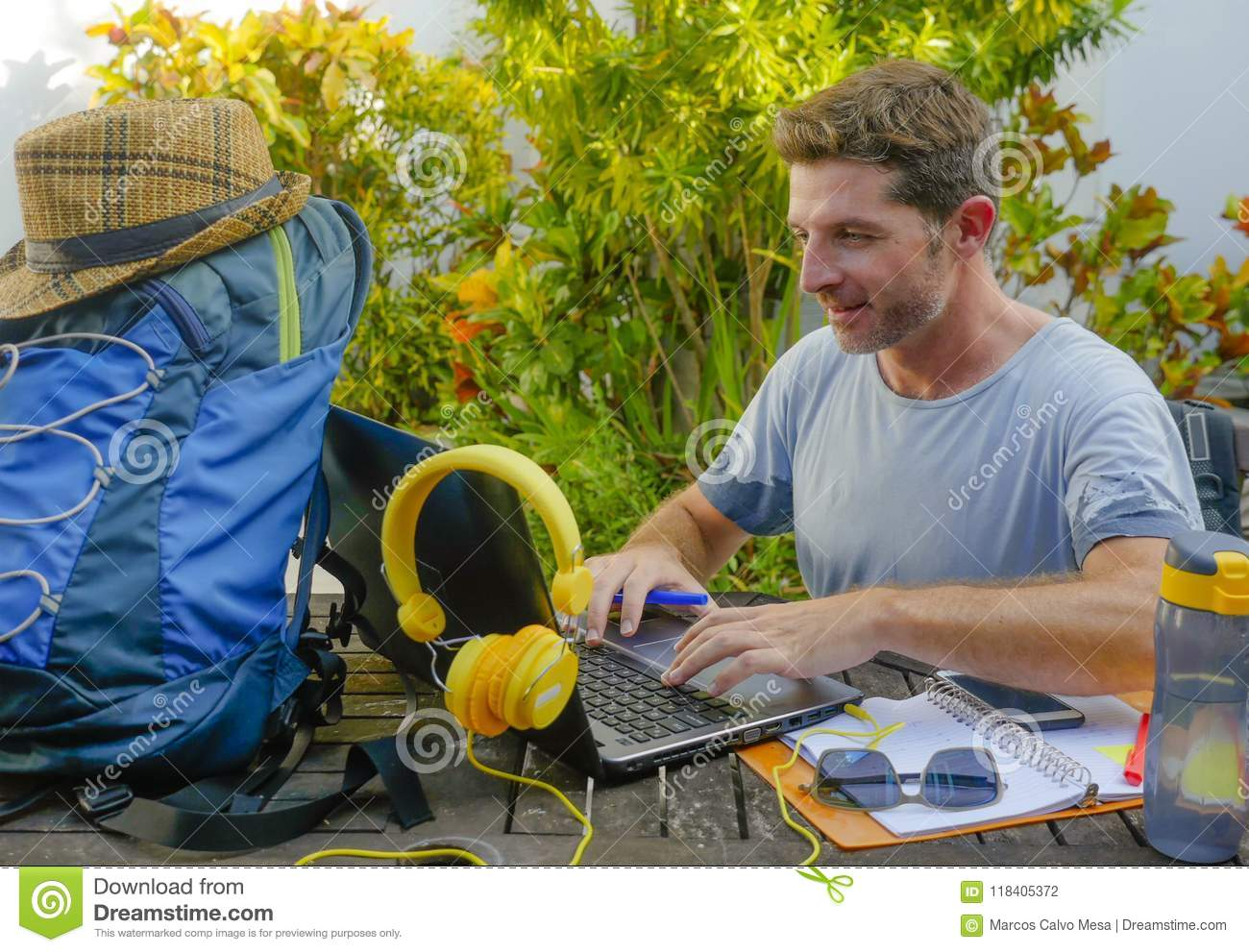 Young attractive and happy digital nomad man working outdoors with laptop computer cheerful and confident running business remote