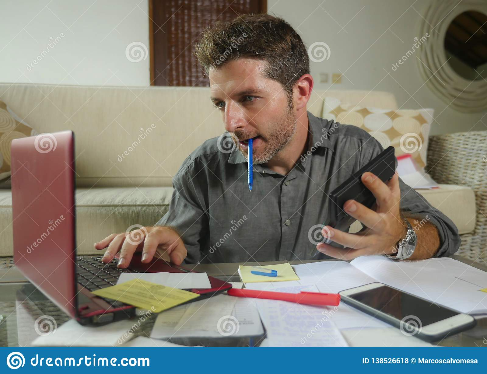 Young attractive and happy freelance business man with calculator and laptop doing domestic accounting paperwork of domestic