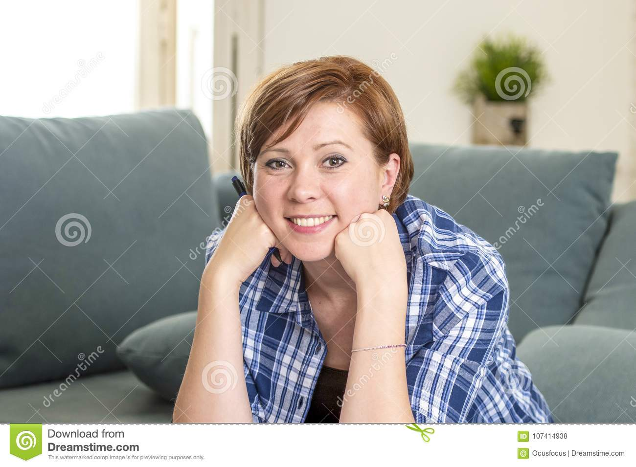 Young attractive and happy red hair woman around 30 years old smiling confident at home living room holding pen in her hand lookin