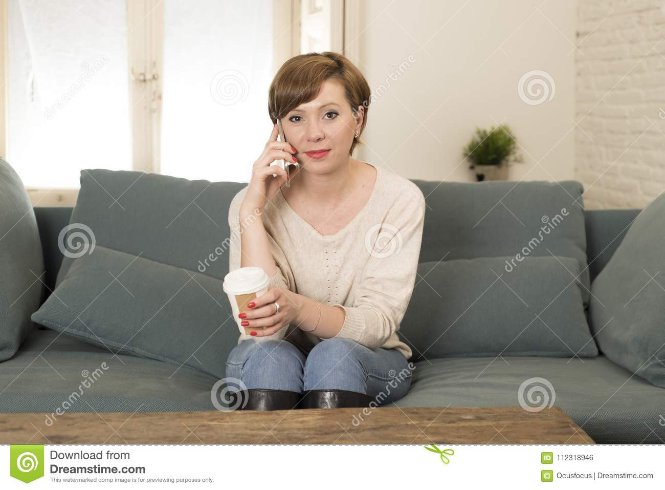 Young attractive and happy red hair woman sitting at home sofa couch drinking coffee talking on mobile phone relaxed in communicat