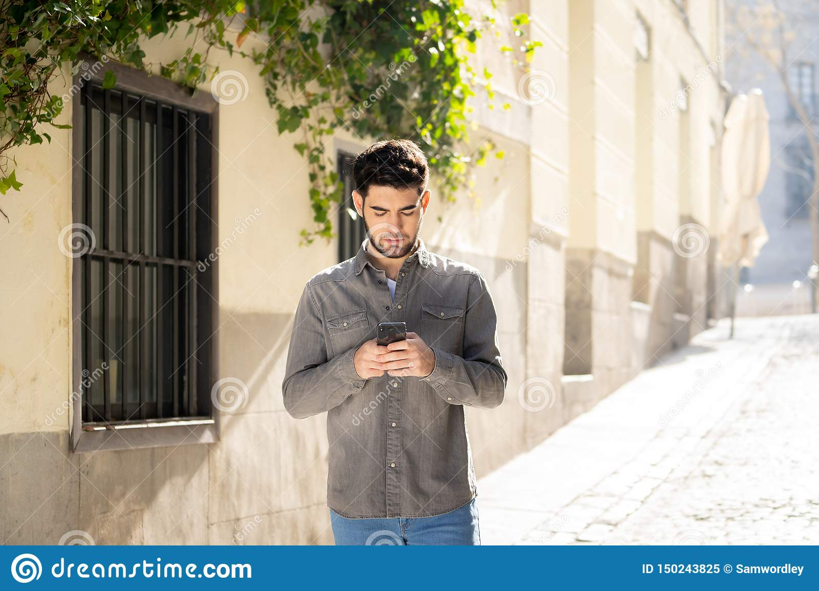 Young attractive happy stylish man on smart phone social network app in european city outdoors