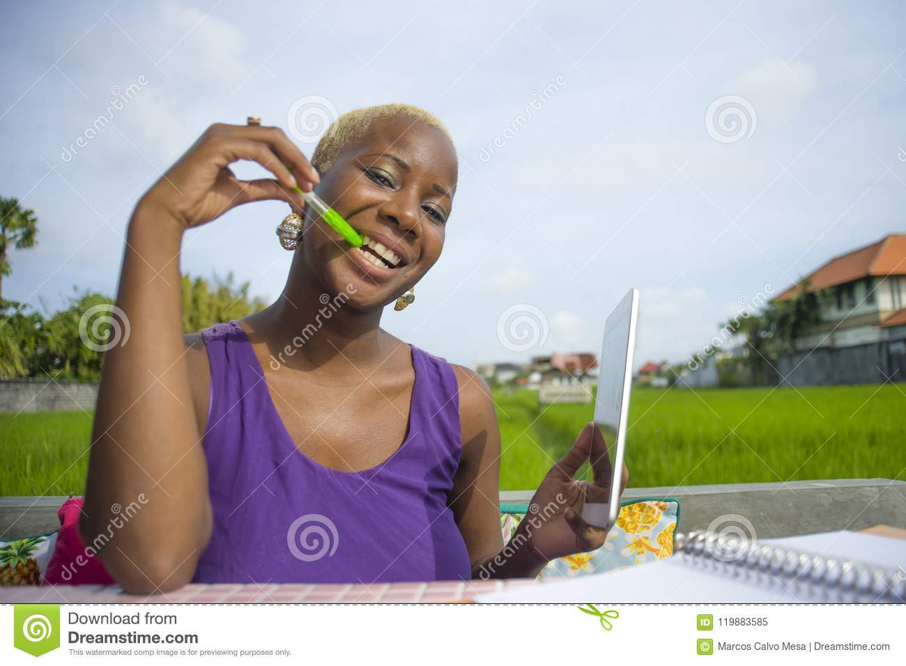 Young attractive and happy successful black afro american woman working with digital tablet pad outdoors on green field cafe smili