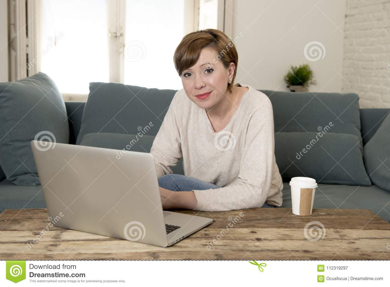 Young attractive and happy woman at home sofa couch doing some laptop computer work smiling relaxed in entrepreneur lifestyle