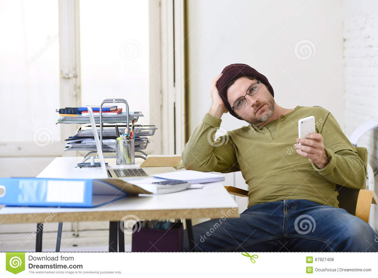 Young attractive hipster businessman working from his home office as freelancer self employed business model
