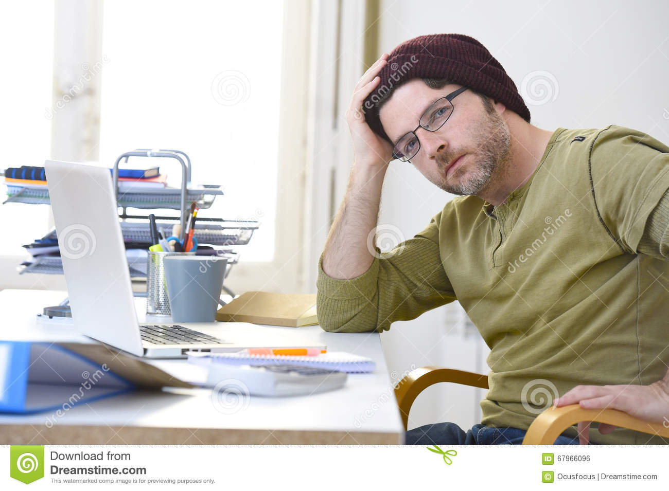 Young attractive hipster businessman working from home office as freelancer self employed business model