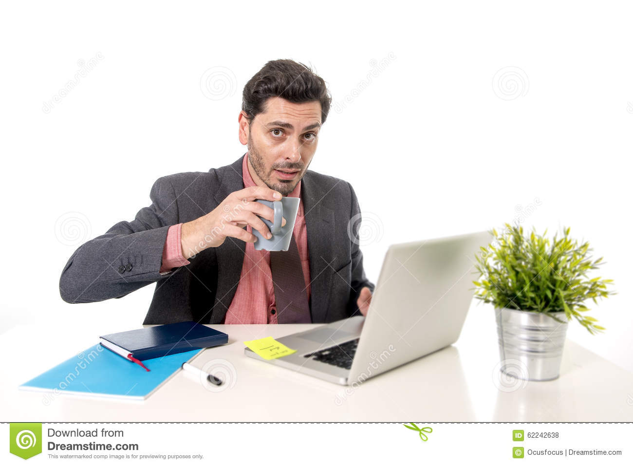 Businessman Sitting At Desk And Drinking Coffee Stock