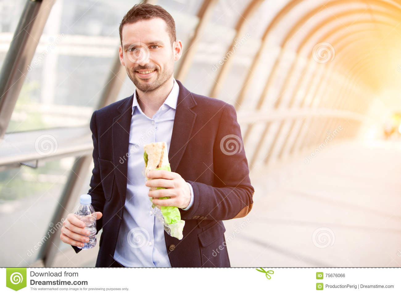 Young attractive man eating fast his lunch