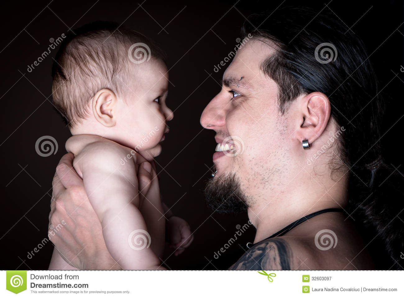 Studio shot of a young father with tattoos holding his infant child