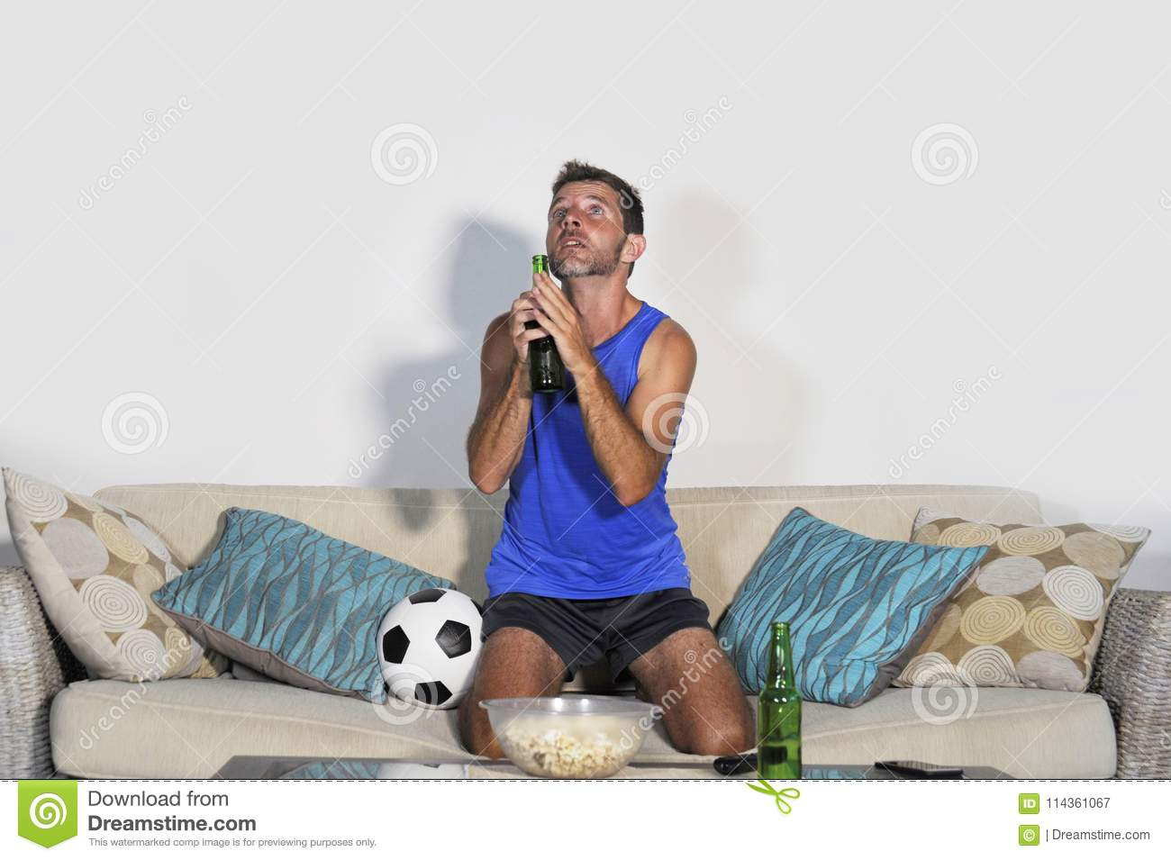 Young Attractive Man Watching Football Game TV Praying