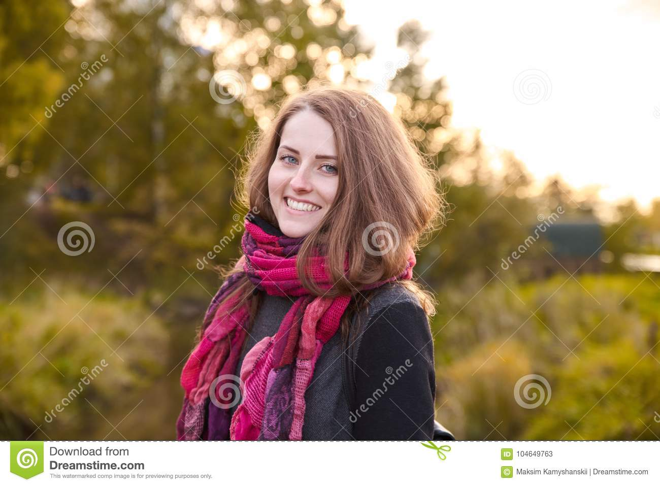 Young attractive red-haired girl posing for a portrait on the ba