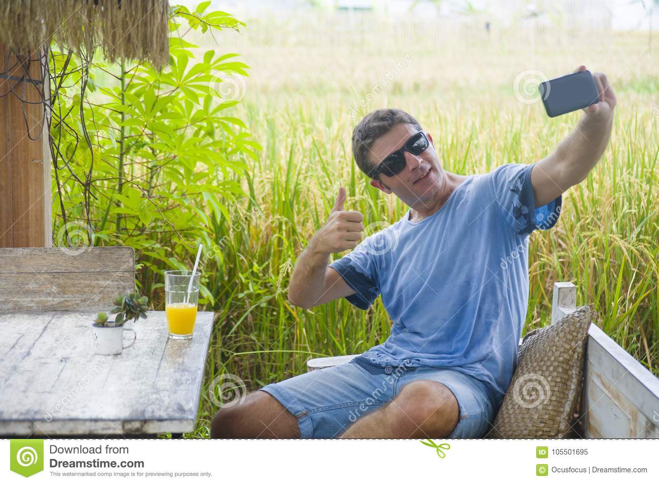 Young attractive 30s Caucasian man smiling happy and relaxed sitting at rice field coffee shop in Asia trip taking selfie picture
