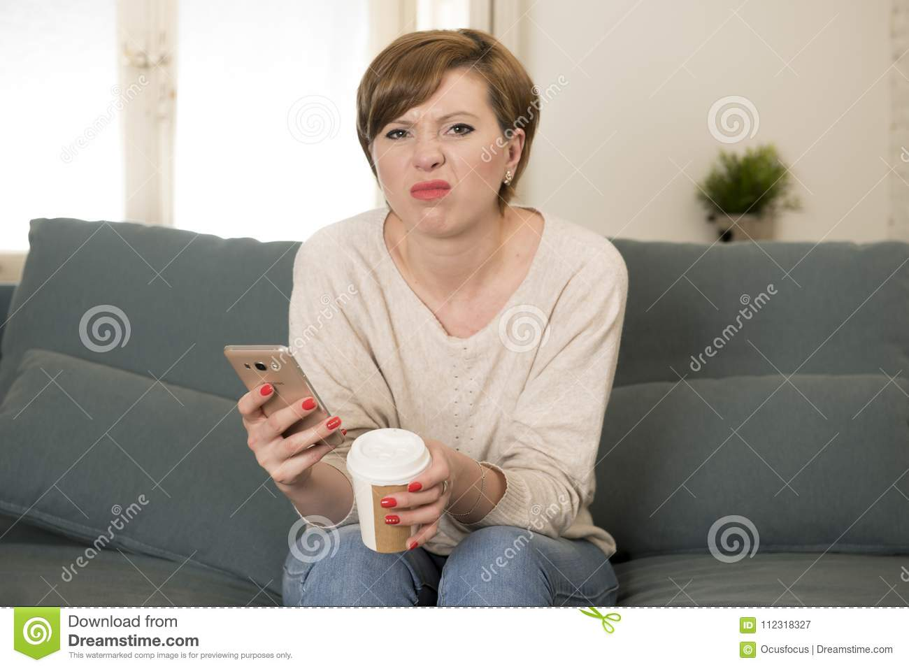 Young Attractive 30s Red Hair Woman Upset Bored And Moody Using Internet  App On Mobile Phone Sitting At Home Sofa Couch In Annoyed Face Expression