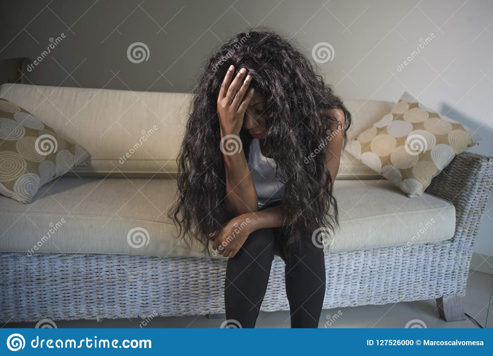 Young attractive and sad black African American woman sitting depressed at home sofa couch feelings anxious and frustrated sufferi