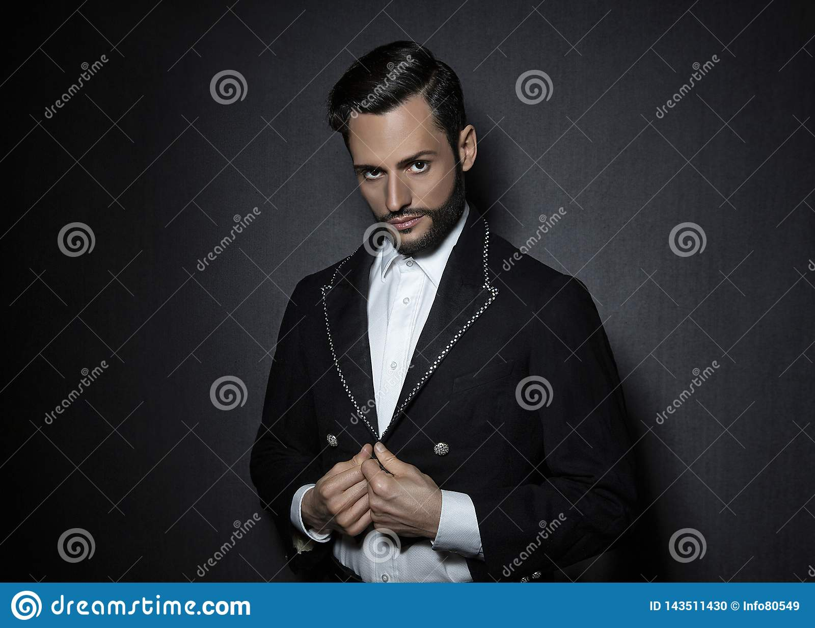 Young attractive, sexy man with beard, dressed in a circus look jacket