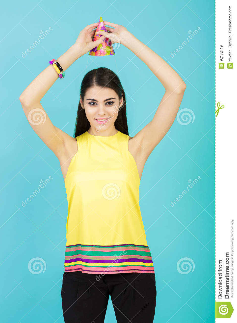 Young attractive smiling woman with birthday hat and whistle on blue background. celebration and party