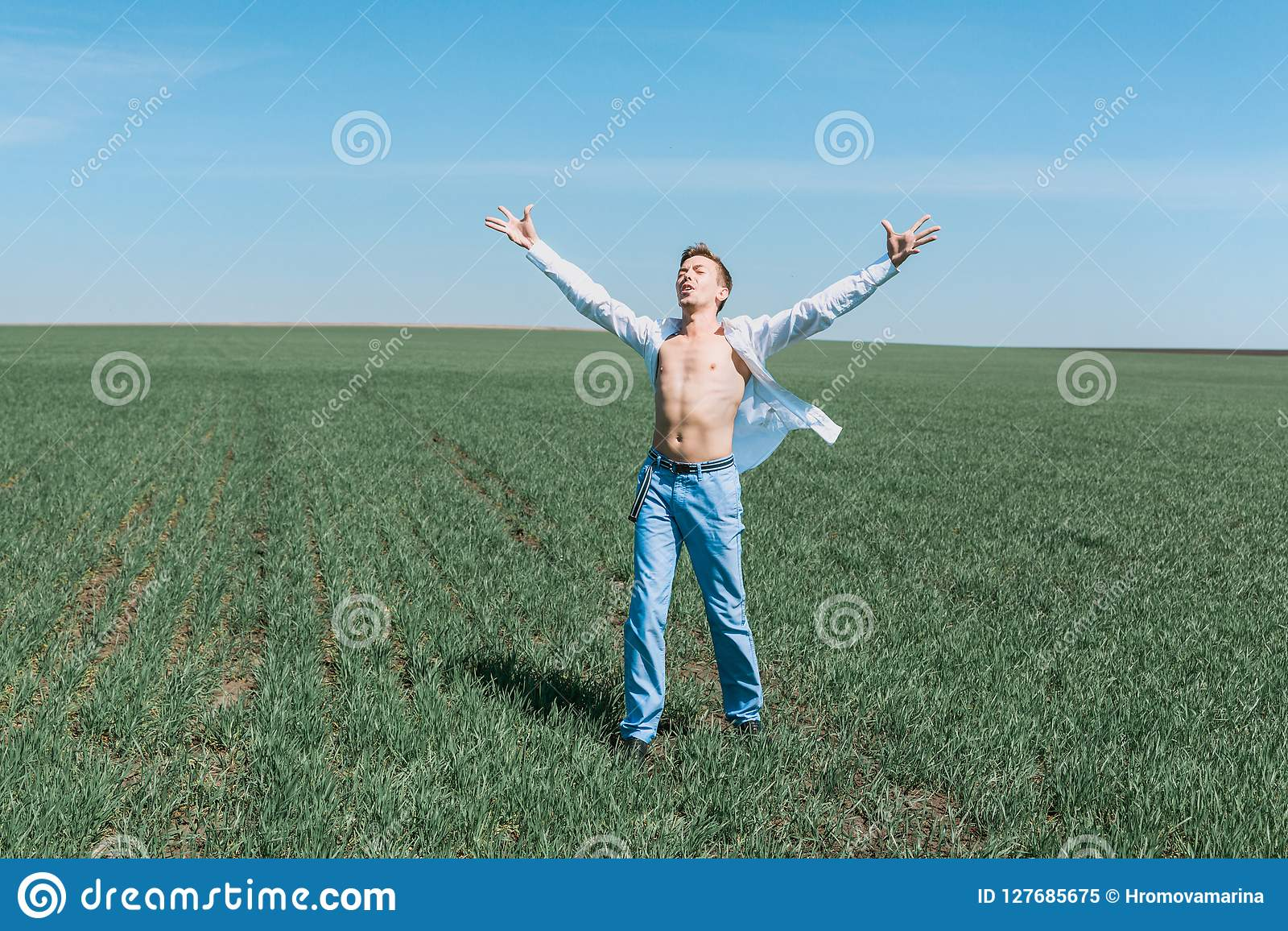 A young attractive sporty man in a white shirt and blue jeans stands in the field.