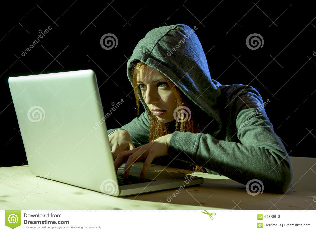 Young attractive teen woman wearing hood on hacking laptop computer cybercrime cyber crime concept