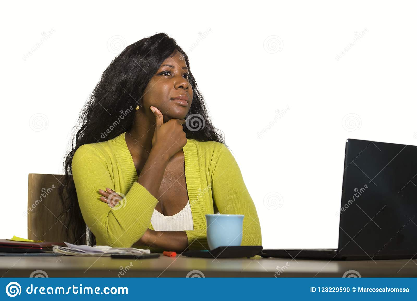 Young attractive and thoughtful black afro American business woman working at office computer desk looking away thinking relaxed i