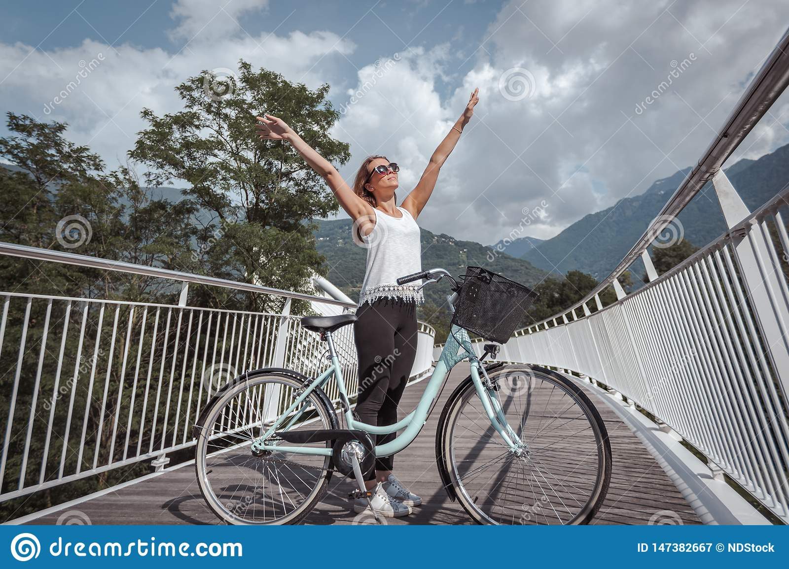 Young attractive woman with bicycle on a bridge