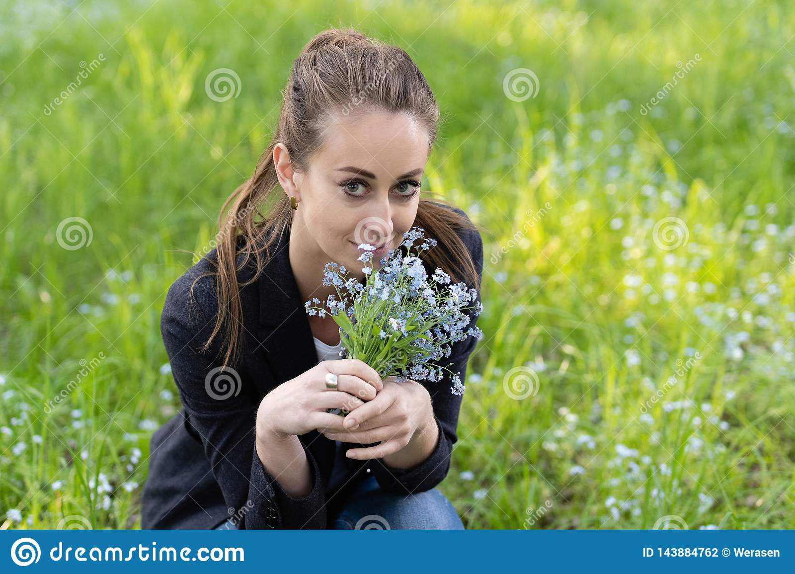 Young attractive woman brought a bouquet of forget-me-nots to her face