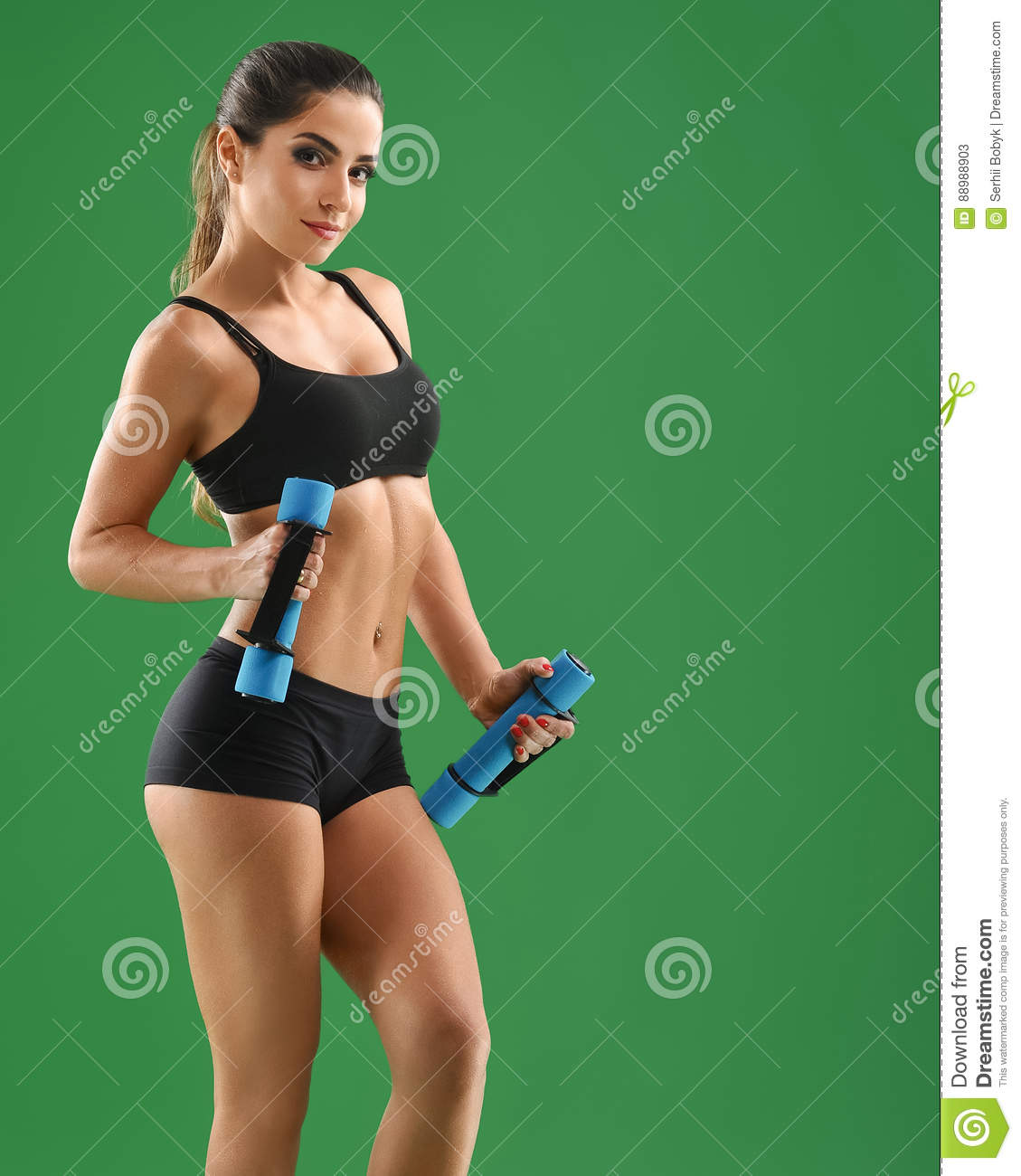 3ddab189a Studio shot of a gorgeous fitness model with perfectly shaped sporty body  exercising with dumbbells smiling happily healthy lifestyle athletics  activity ...