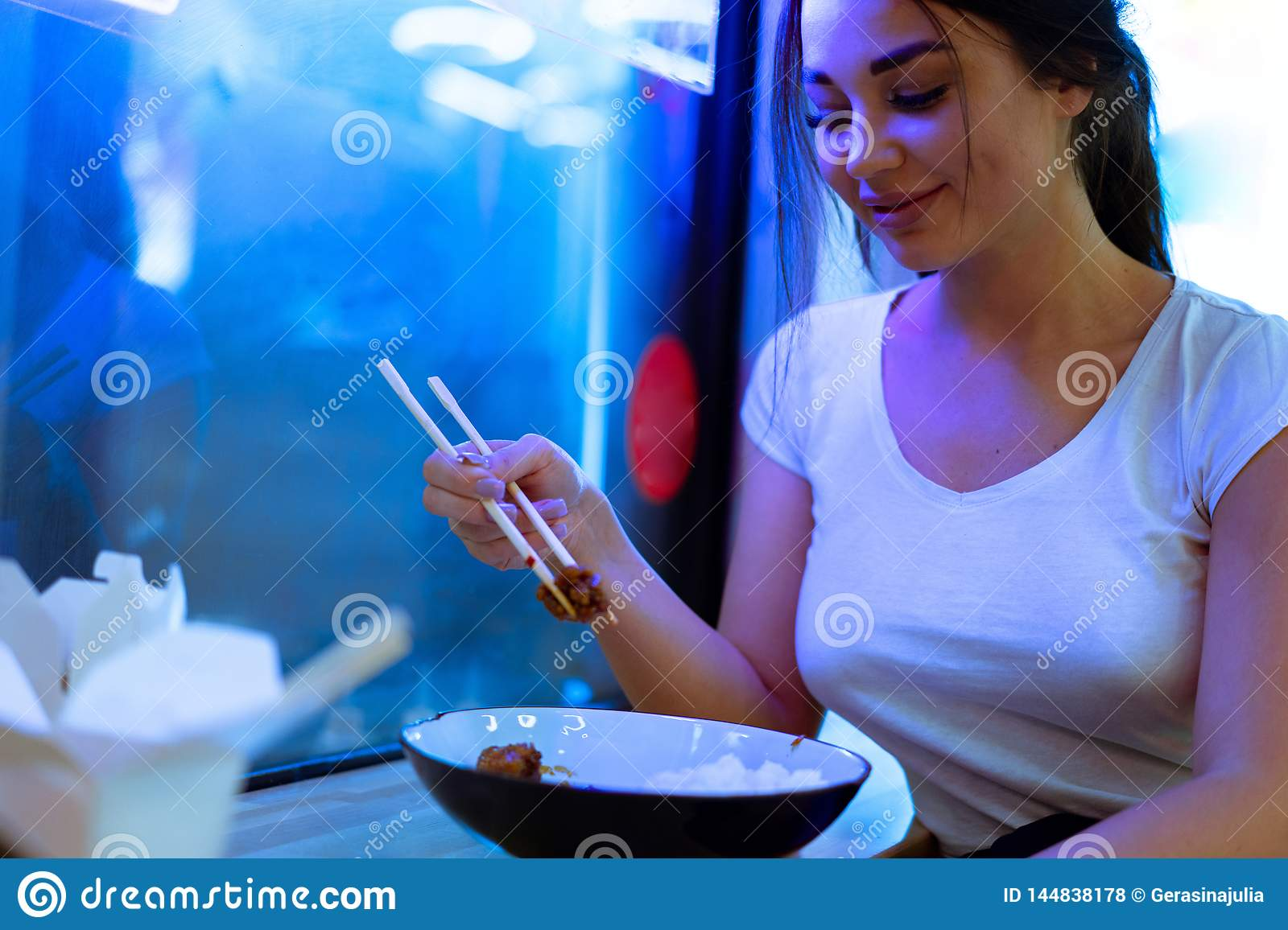 Young attractive woman eating asian food with chopsticks at cafe or restaurant.