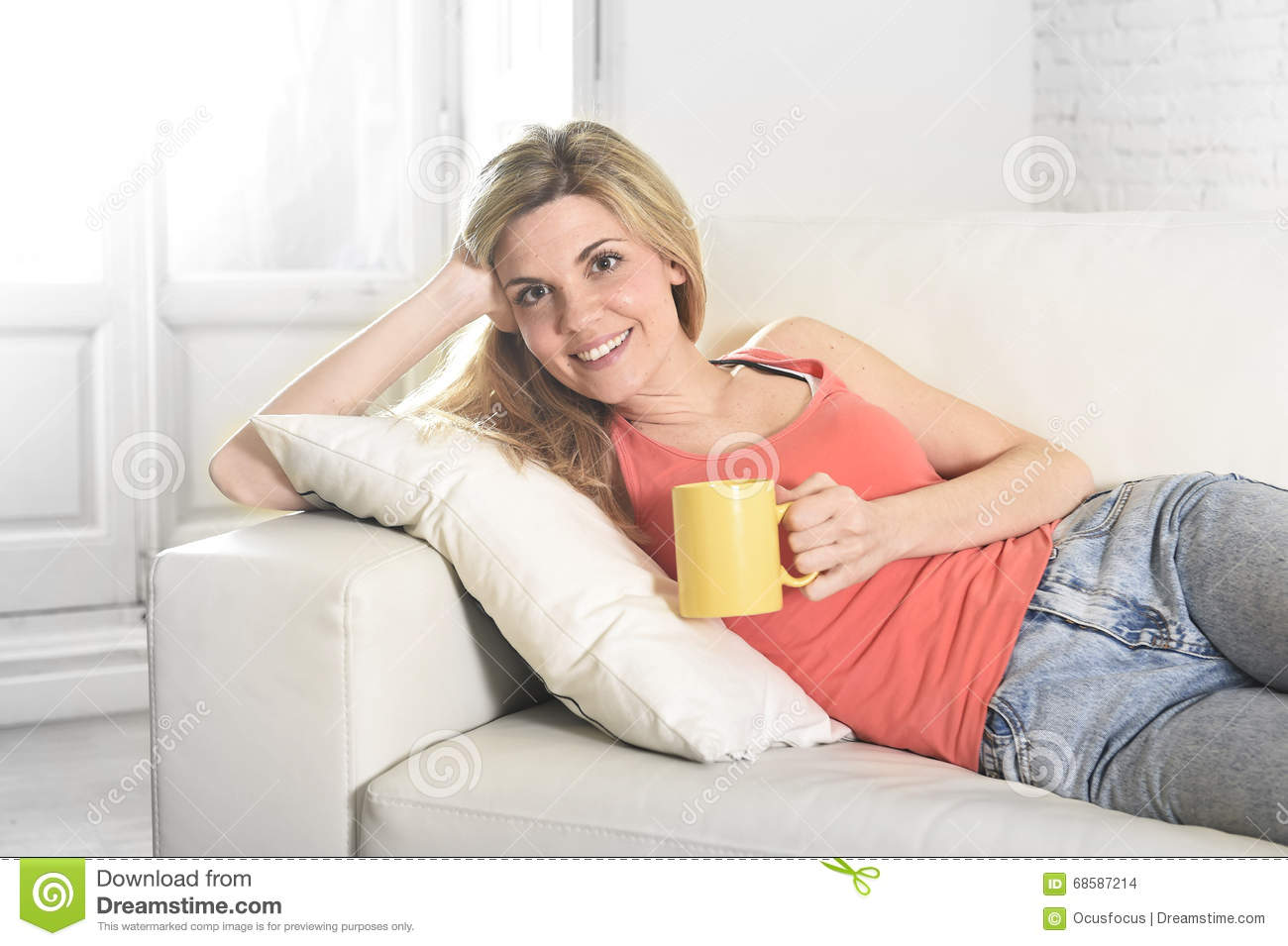 Young attractive woman holding cup of coffee sitting on sofa couch at home smiling happy