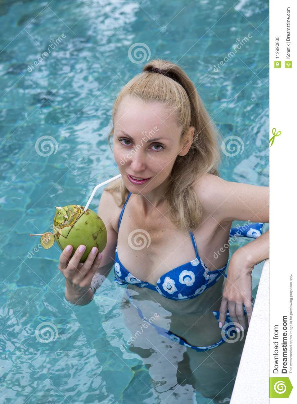 Young attractive woman with long hair in a swimwear in the pool with cocktail in coconut