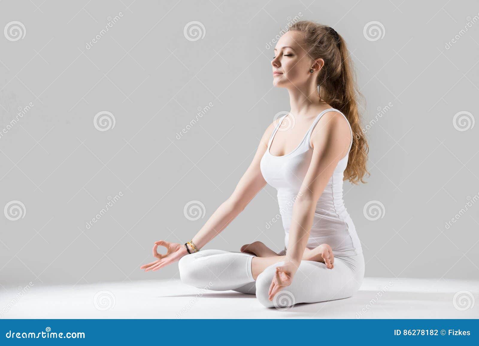 Young attractive woman in Padmasana pose with mudra, grey studio