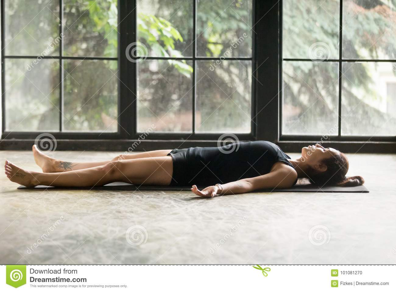 young attractive woman in corpse pose studio background stock photo