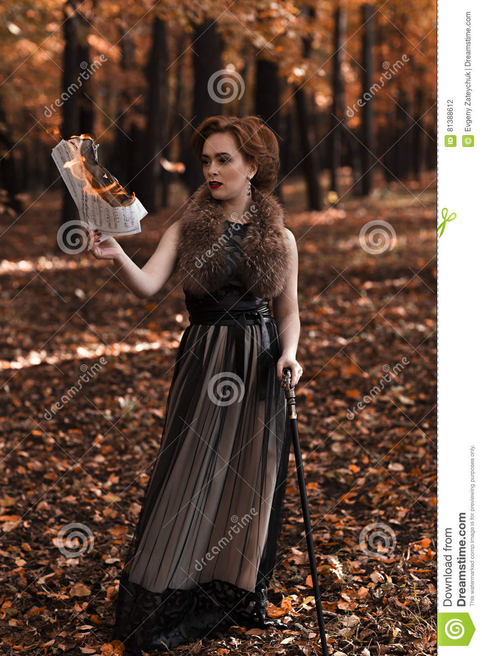 young attractive woman standing in fall park and holding burning