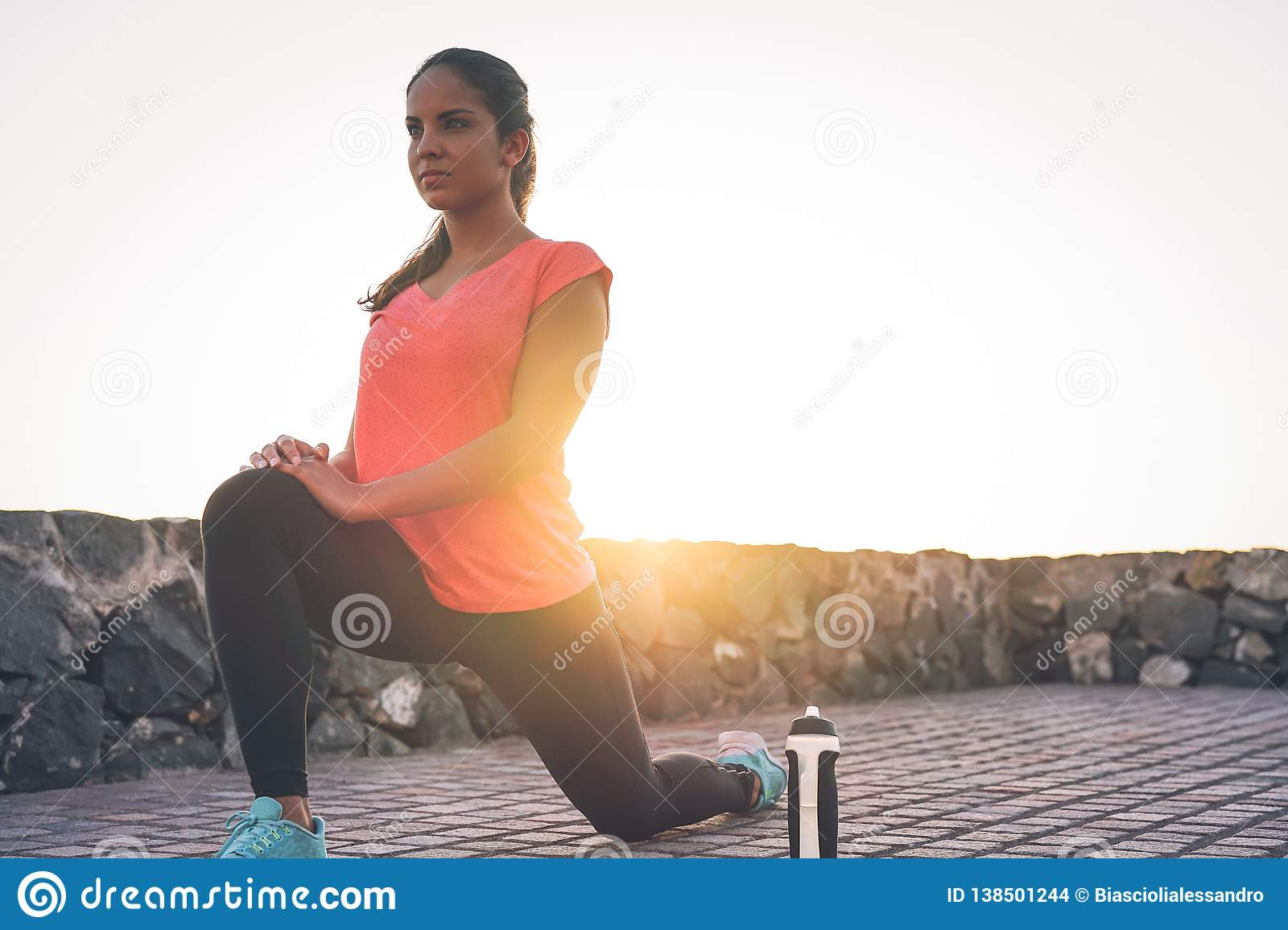 Young attractive woman stretching next the beach during a magnificent sunset - Sporty health girl workout outdoor