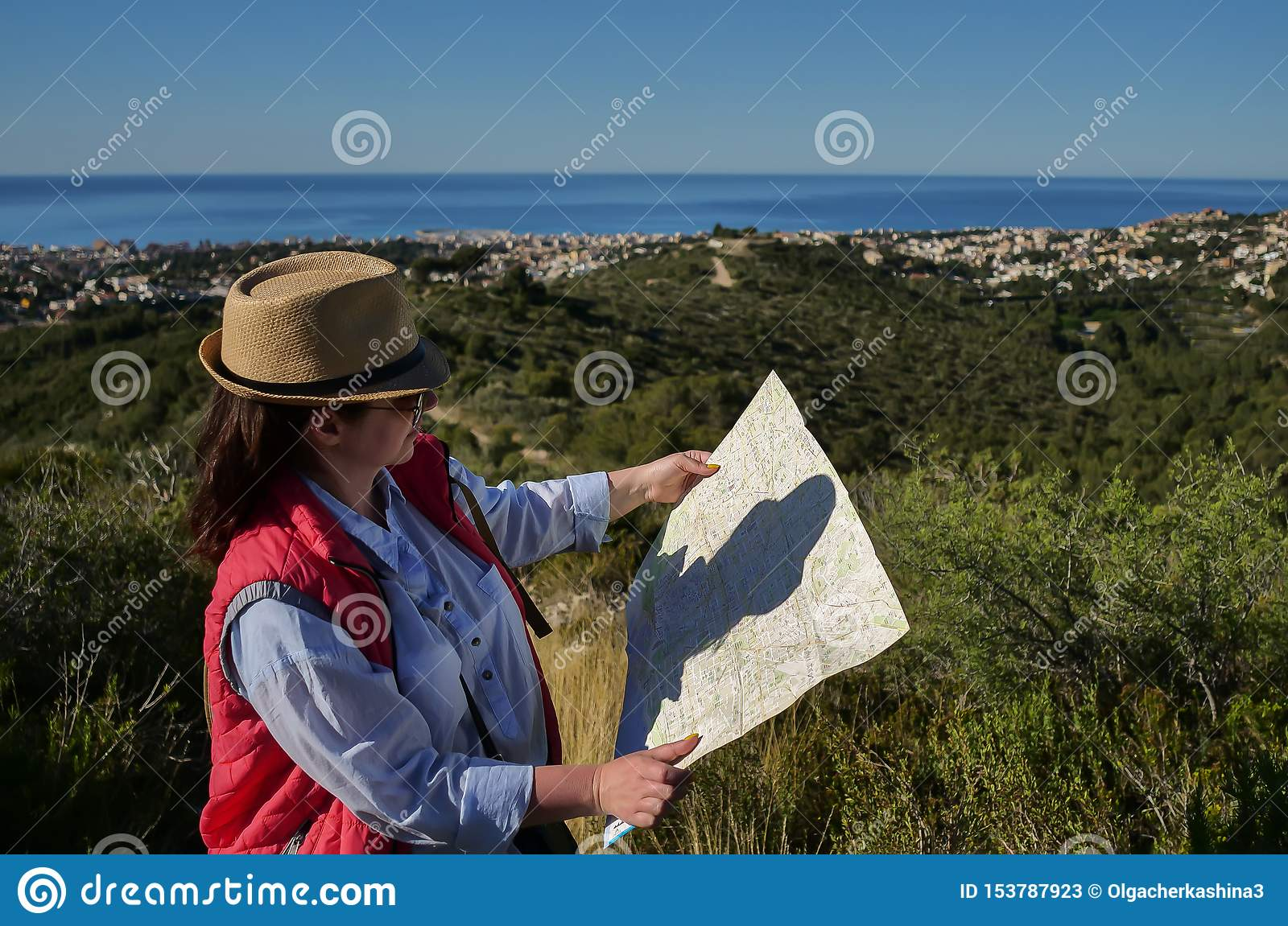 Young attractive woman tourist with hat and map of the area looks at the city under the hill