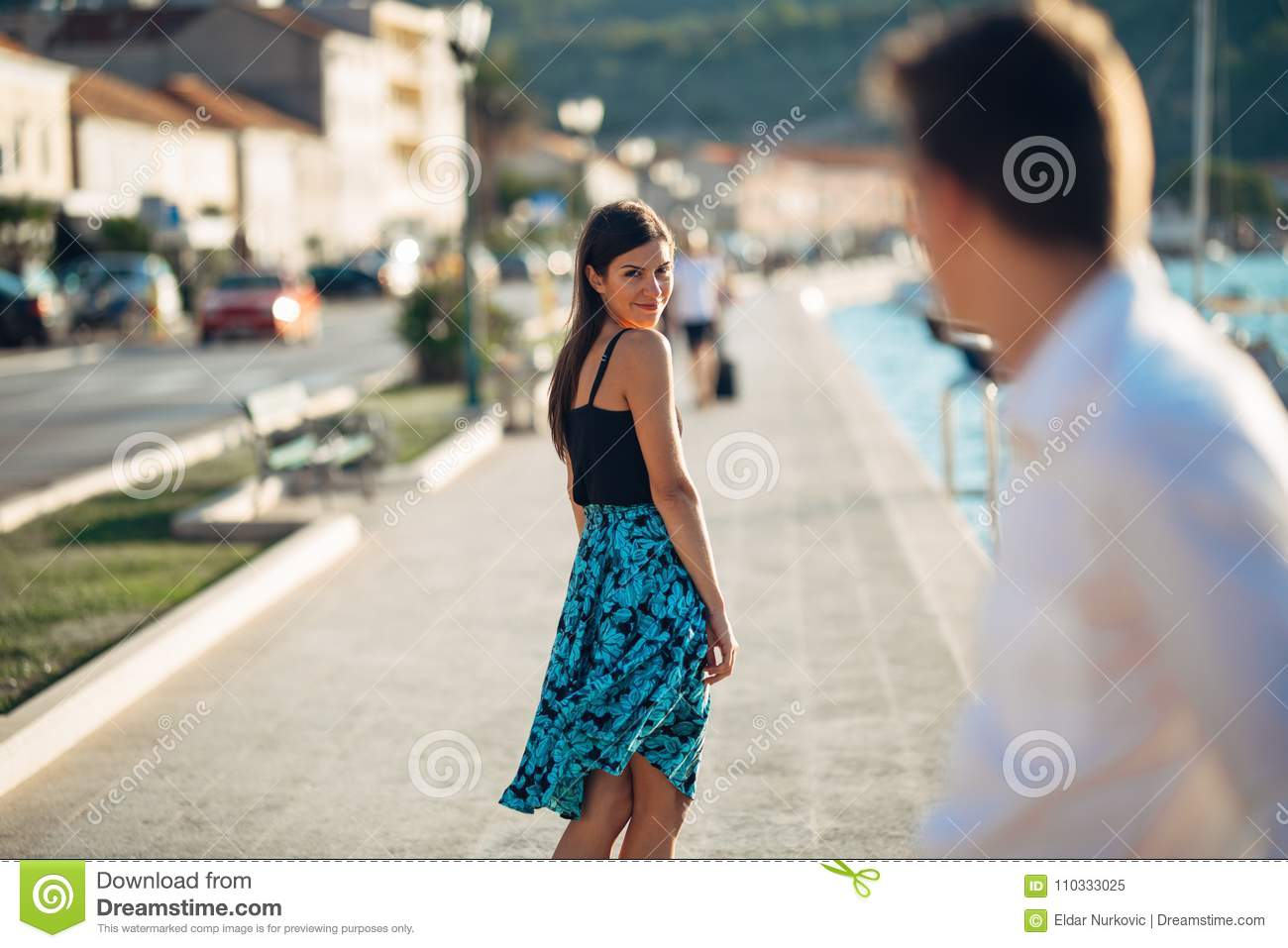 Young attractive woman flirting with a man on the street.Flirty smiling woman looking back on a handsome man.Female attraction