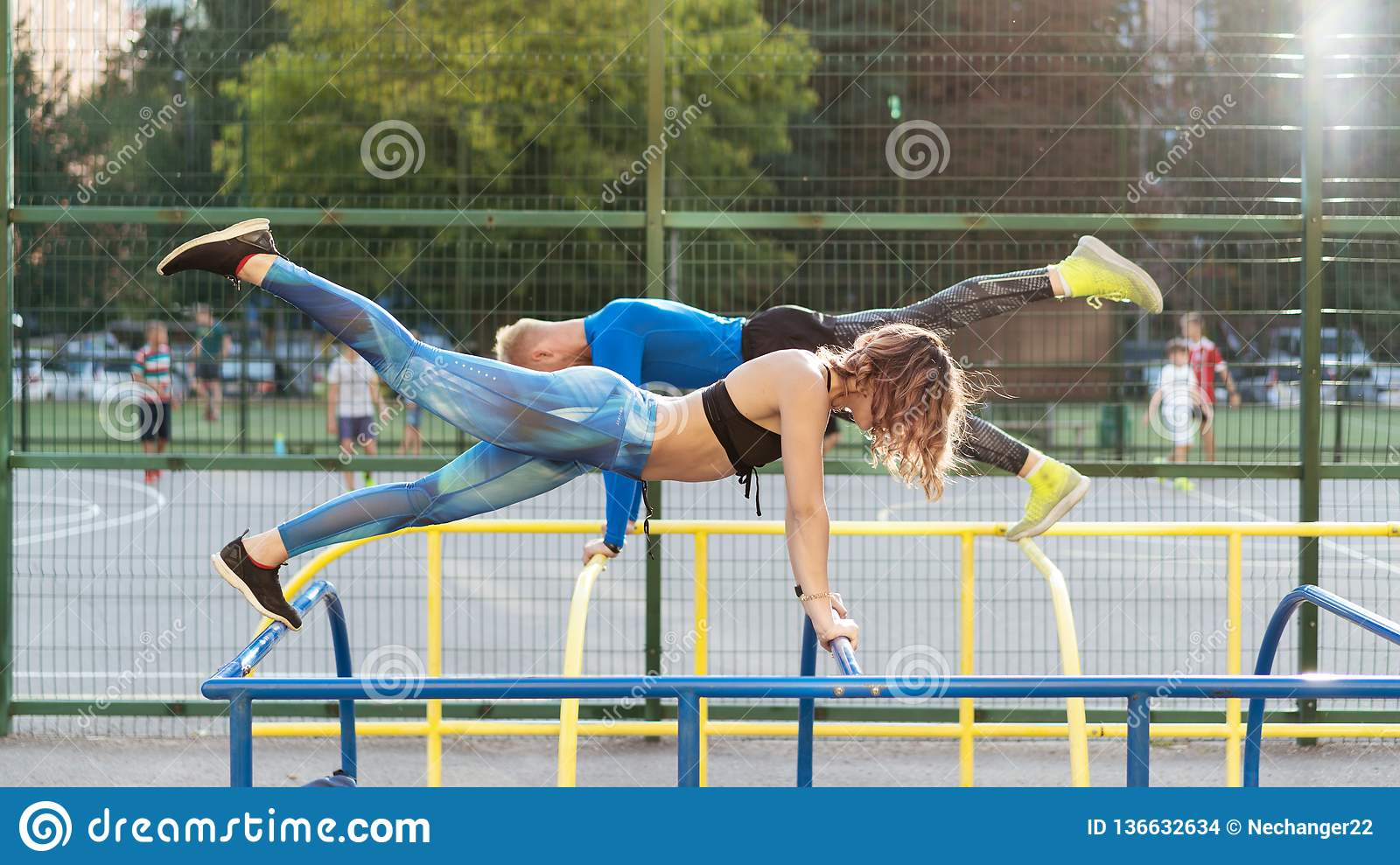 Young attrective crossfit man and woman working out on the sportsground