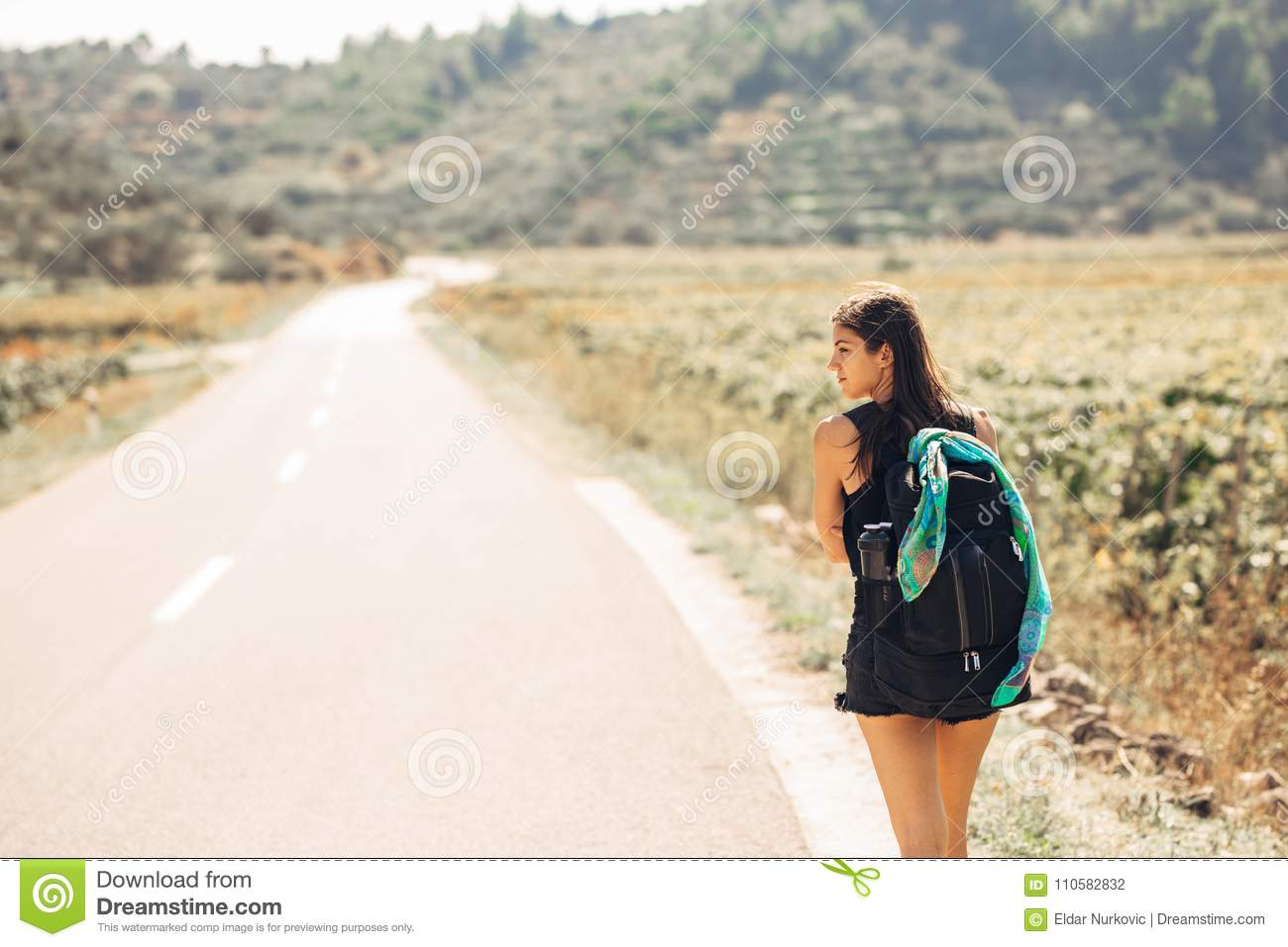 Young Backpacking Adventurous Woman Hitchhiking On The ...
