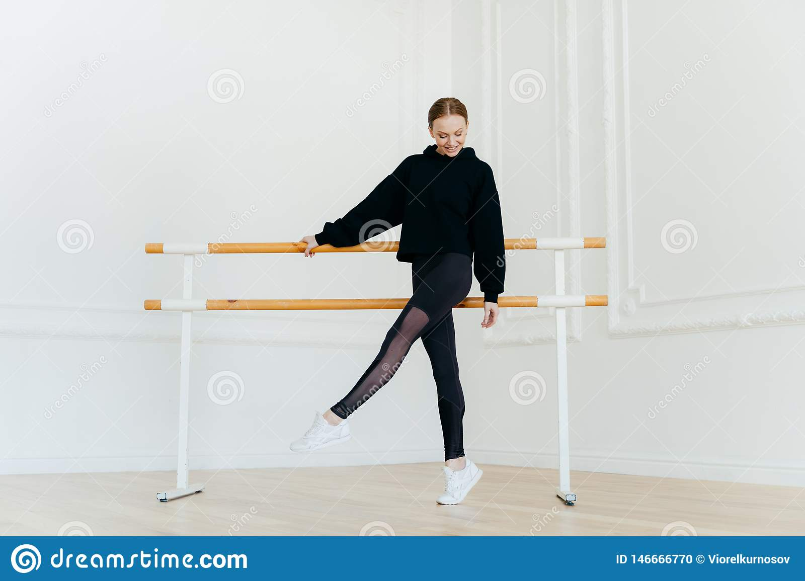 Young ballet dancer has warm up, stands near handrails, dressed in black sportclothes, stands on tip toe, wears white sneakers,