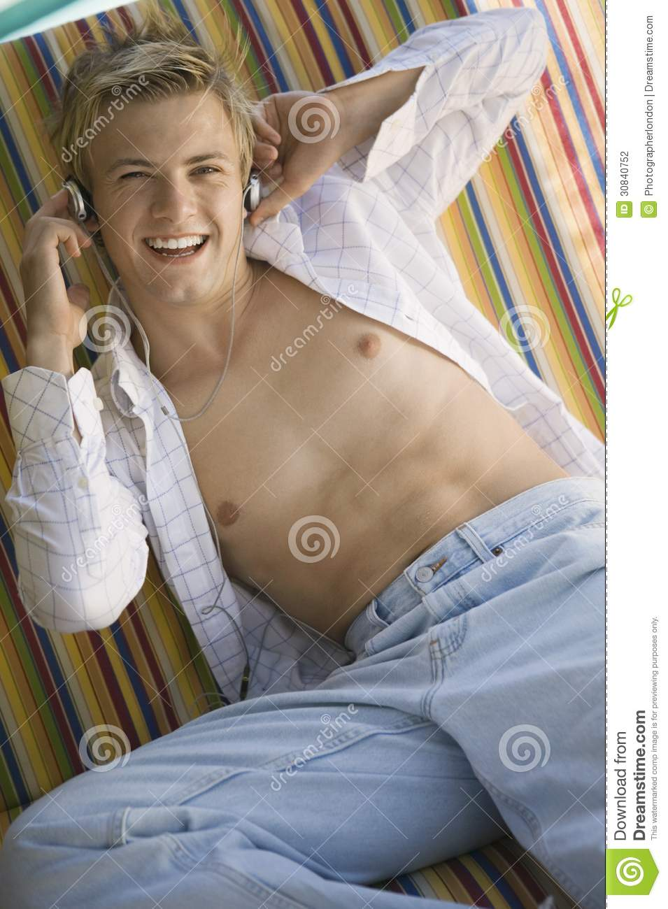 Young Bare-chested Man On Deckchair Listening To Music On ...