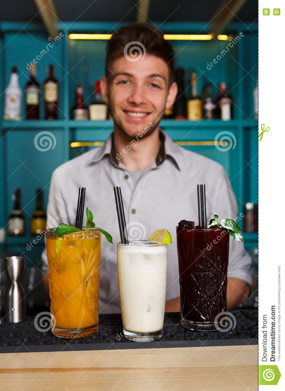 Young Barman offers alcohol cocktails in night club bar
