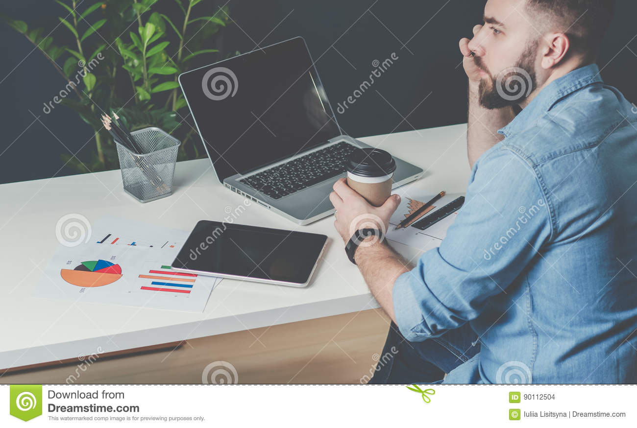 Young bearded businessman in denim shirt is sitting at office at table, talking on mobile phone and drinking coffee.
