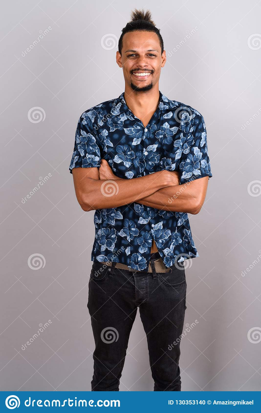 6f825110c Studio shot of young bearded handsome African man wearing Hawaiian shirt  with hair tied against gray background
