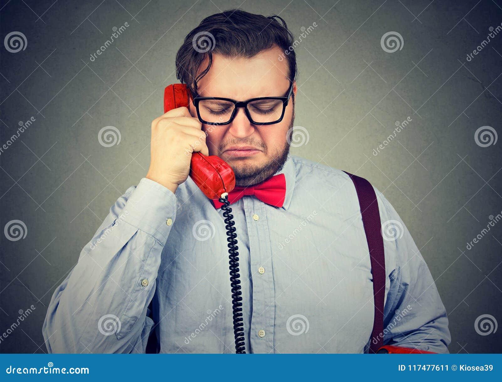 Heartbroken sad man talking on telephone and looking unhappy feeling devastated