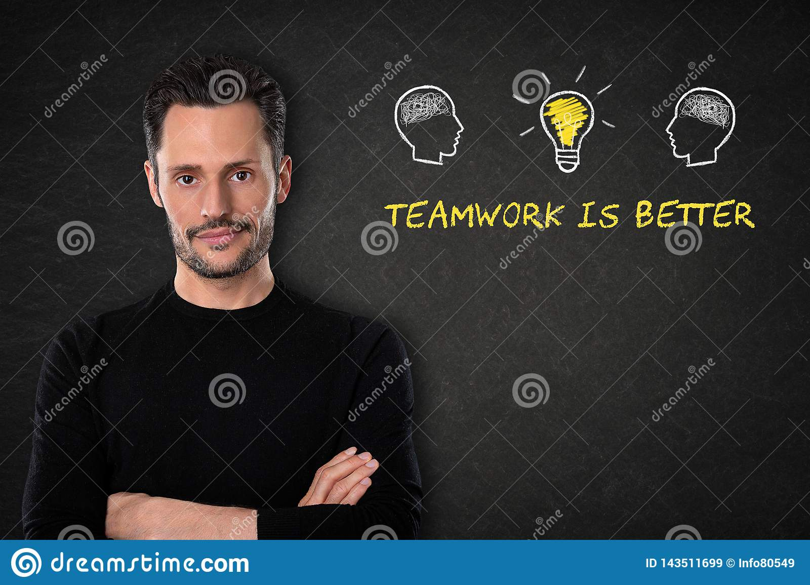 Young bearded man with crossed arms, heads with brains, lightbulb-idea and text `Teamwork is better` on a blackboard background.